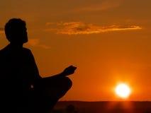 El Meditating en la puesta del sol Fotos de archivo
