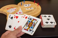 El mejor del juego de tarjeta del cribbage entrega un tablero del juego fotografía de archivo libre de regalías