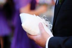 El mejor hombre que sostiene una almohadilla con los anillos de bodas Fotos de archivo