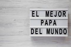 'El Mejor Papa Del Mundo 'ord på ett modernt bräde över vit träbakgrund, bästa sikt ?ver huvudet fr?n ?ver, framl?nges lekmanna-  royaltyfria bilder