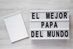 `El Mejor Papa Del Mundo` words on modern board, blank notepad over white wooden background, top view. Overhead, from above, fla royalty free stock photo