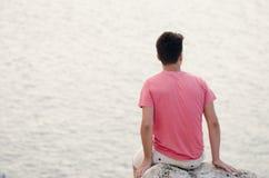 El melancholic del adolescente se sienta con la parte posterior encima de la piedra grande que mira a Fotos de archivo