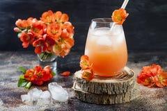 El melocotón en colores pastel floral y el cóctel rosado del brunch adornados con el membrillo florece sobre viejo fondo rústico Foto de archivo