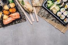 El menú del sushi con nigiri, maki y el interior rueda, verano rueda en las envolturas de papel de arroz en gris en el fondo de p fotografía de archivo