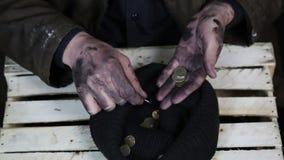 El mendigo considera monedas metrajes