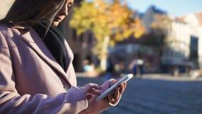 El mensaje que mecanografía de la mujer joven, amigos que esperan en la calle, permanece en contacto concepto almacen de video