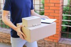 El mensajero Brings Order del hombre al cliente, da la pluma y el papel a los Sig Fotos de archivo libres de regalías