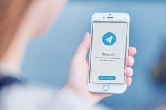El mensajero del telegrama en el iPhone de Apple en mujer entrega la opinión del hombro Foto de archivo