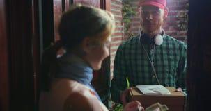 El mensajero entregó la pizza y recibió el pago usando tarjeta del terminal y de crédito metrajes