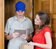 El mensajero joven entrega el paquete Foto de archivo libre de regalías
