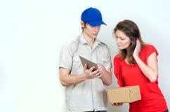 El mensajero joven entrega el paquete Fotografía de archivo libre de regalías
