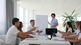 El mentor femenino cerca de Whiteboard con la carta habla con los colegas sobre el desarrollo de negocios en la sala de reunión metrajes