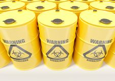 El metal amarillo barrels con la señal de peligro negra del biohazard en el fondo blanco Foto de archivo