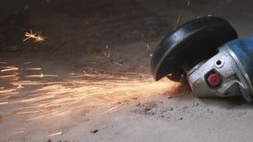 El metal circular vio cortar una pieza de metal en chispas anaranjadas de la generación concreta del piso El trabajador corta el  almacen de metraje de vídeo