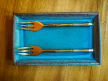 El metal gemelo bifurca en platos en la tabla de madera para el desayuno por la mañana Imagen de archivo libre de regalías