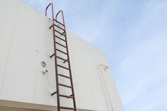 El metal industrial vertical viejo de la escalera aherrumbró al tanque de agua Imagenes de archivo