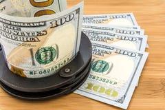 El metal negro esposa la mentira en los 100 dólares de billetes de banco Imágenes de archivo libres de regalías