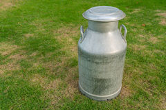 El metal viejo puede en la leche en yarda verde Imágenes de archivo libres de regalías