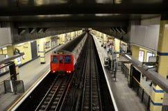 El metro subterráneo del tubo de Londres sale de la plataforma de la estación Fotos de archivo libres de regalías