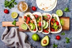 El mexicano asó a la parrilla los tacos de pollo con el aguacate, tomate, cebolla en la tabla de piedra rústica Receta para el pa Fotografía de archivo