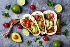 El mexicano asó a la parrilla los tacos de pollo con el aguacate, tomate, cebolla en la tabla de piedra rústica Receta para el pa imagen de archivo