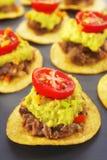 El mexicano muerde el comida para comer con los dedos del aperitivo de los Nachos Imagen de archivo libre de regalías