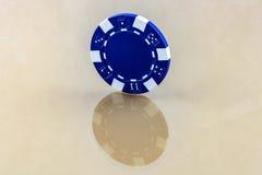 El microprocesador azul del casino se coloca en la superficie reflectora Imagenes de archivo