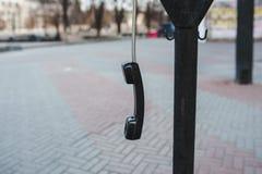 El microteléfono cuelga en la calle en un alambre Fotografía de archivo