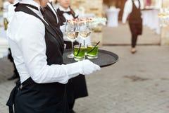 El Midsection de camareros profesionales en vino uniforme de la porción, los cócteles y los bocados durante el abastecimiento de  Imagen de archivo