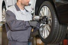 El Midsection del mecánico de sexo masculino que repara el coche rueda adentro el taller foto de archivo