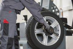 El Midsection del mecánico de sexo masculino que repara el coche rueda adentro el taller de reparaciones fotos de archivo