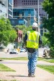 El miembro del equipo de construcción toma una rotura y camina abajo del paseo lateral en el centro de la ciudad Fotos de archivo libres de regalías