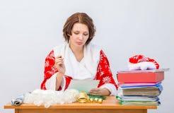 El miembro del personal de la oficina de la muchacha vestido como Santa Claus lee un documento con una pluma en sus manos Fotografía de archivo libre de regalías