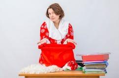 El miembro del personal de la oficina de la muchacha vestido como Santa Claus muestra un bolso vacío para los regalos Foto de archivo libre de regalías