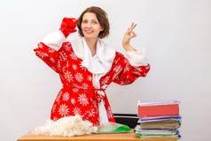 El miembro del personal de la oficina de la muchacha vestido como Santa Claus que muestra los pulgares sube el gallo Fotografía de archivo