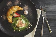 El milhojas de la cereza y de manzana sirvió con una cucharada del helado de vainilla en una placa negra de cerámica Visión desde fotos de archivo