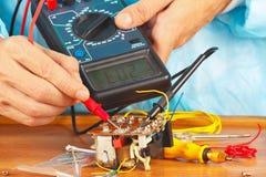El militar comprueba componentes electrónicos del dispositivo con el multímetro Fotografía de archivo