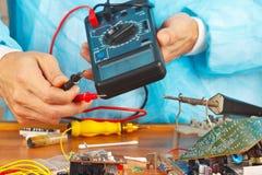 El militar comprueba el tablero de dispositivo electrónico con un multímetro Fotos de archivo