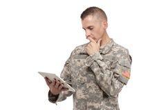 El soldado de sexo masculino mira su tableta fotos de archivo