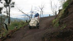El minero tira de un carro desde arriba del volcán activo de Kawah Ijen con una carga del azufre minado imagen de archivo libre de regalías
