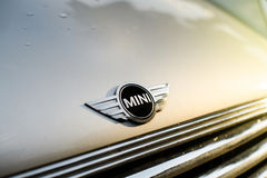 El mini coche parqueó en ciudad con el mini logotipo Foto de archivo libre de regalías