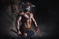El minotaur enojado del hombre del bodyart con el hacha en cueva Fotos de archivo
