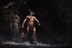 El minotaur enojado del hombre del bodyart con el hacha en cueva Imágenes de archivo libres de regalías