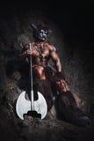 El minotaur enojado del hombre del bodyart con el hacha en cueva Fotos de archivo libres de regalías
