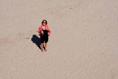 El mirar abajo una mujer que se coloca en arena Foto de archivo