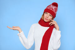 El mirar de pensamiento de la mujer hermosa joven al lado con mostrar la palma abierta de la mano el sombrero que lleva en blanco Imagen de archivo