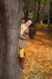 El mirar a escondidas detrás del árbol en otoño Imágenes de archivo libres de regalías