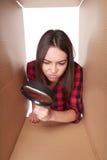 El mirar a escondidas femenino en la caja del cartón que mira a través de la lupa Imágenes de archivo libres de regalías