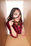 El mirar a escondidas femenino en la caja del cartón que mira a través de la lupa Foto de archivo