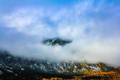 El mirar a escondidas superior de la montaña a través de las nubes Imágenes de archivo libres de regalías